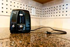 Unplugged toaster on a kitchen counter with an electrical outlet in the background