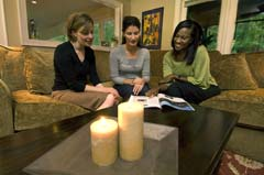 Three women looking at magazine with candles in foreground