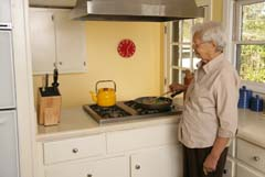 Older woman at cook top stirring food in skillet; full shot of woman