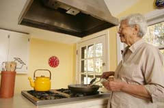 Older woman at cook top stirring food in skillet; holding bottle of seasoning and smiling