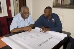 Older African American man with fire personnel reviewing plan at table