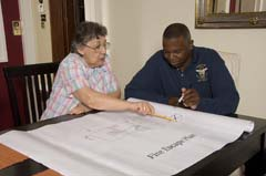 firefighter and older adult reviewing a fire escape plan