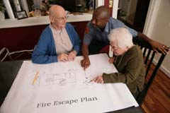Older adults with fire personnel in center (older woman pointing at escape plan)