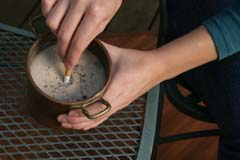 Close up of hand extinguishing cigarette in urn with sand
