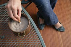 One hand seen extinguishing cigarette in urn with sand; legs visible (outdoors)