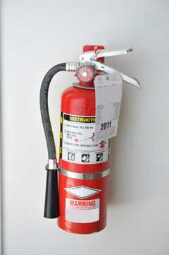 Wall-mounted fire extinguisher with service tag