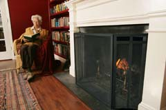Fireplace screen in foreground; older woman reading to right; shot closer and lower