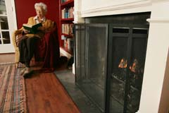 Low shot of fireplace screen in foreground; woman in chair at right