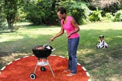 Woman grilling outside with a child outside a 3-foot safety zone around the grill
