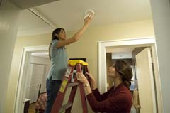 Two women installing alarm; ladder