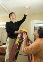 Asian-American man on ladder installing alarm; second Asian man holding ladder