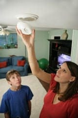 Caucasian woman installing smoke alarm; teen looking on