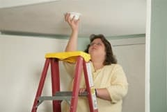 Caucasian woman installing smoke alarm on ladder