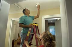 Hispanic man on ladder installing alarm; wife holding ladder