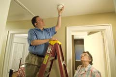 Caucasian man on ladder installing alarm; older Caucasian woman looking on (alarm snug to base)
