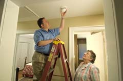 Caucasian man on ladder installing alarm; older Caucasian woman looking on (alarm slightly away from base)