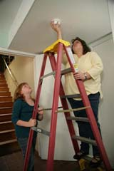 Mother and child installing alarm (mother on ladder)