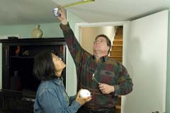 Native American Indian couple installing alarm with tape measure