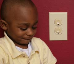 Close crop of African American child by outlet covers