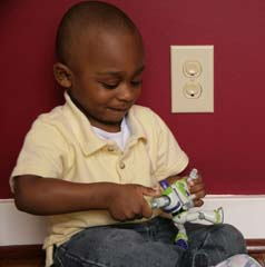 African American child by outlet covers (with Buzz Lightyear)