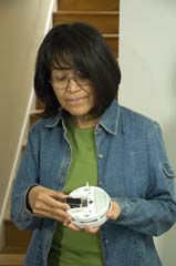 Native American Indian woman replacing alarm batteries