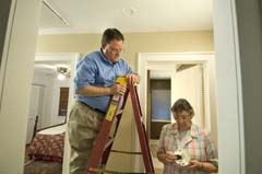 Older Caucasian woman replacing batteries in alarm; Caucasian man on ladder looking on