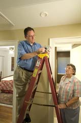 Caucasian man on ladder replacing batteries; older Caucasian woman looking on