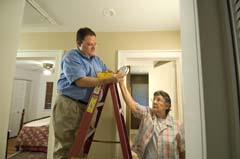 Older Caucasian woman handing alarm to Caucasian man on ladder