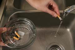 Closer shot of hand holding cigarette under running water; ashtray in view