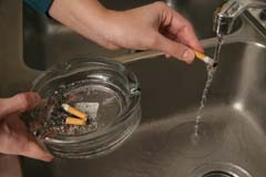 Hand holding cigarette under running water; ashtray with cigarettes also in view with fuller hand