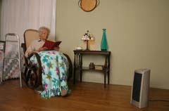 Space heater off to right; woman in chair on left; blanket and walker visible