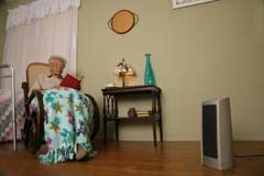 Lower shot of space heater off to right; woman in chair on left; blanket and 1/4 of walker visible