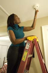 African American woman on ladder testing alarm