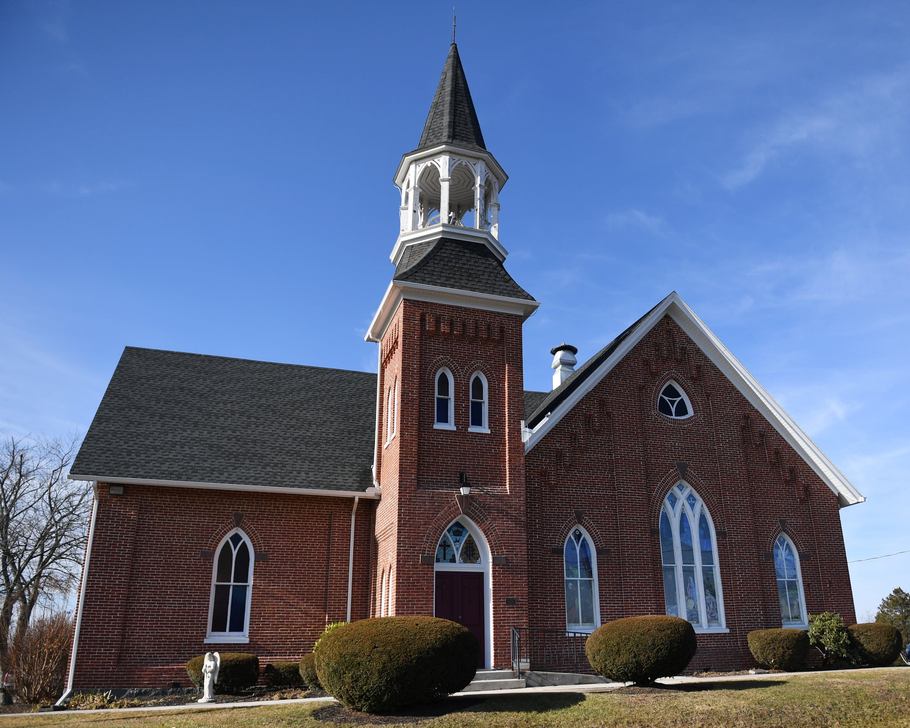 A photo of a house of worship on a sunny day, with a bright blue sky, green grass, and the building set in the middle. The building is made out of brick and features a large steepl.