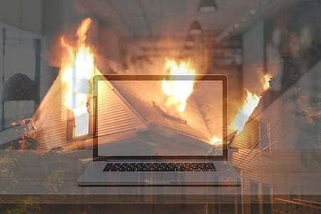 a blank laptop monitor screen overlayed on a photo of a house fire