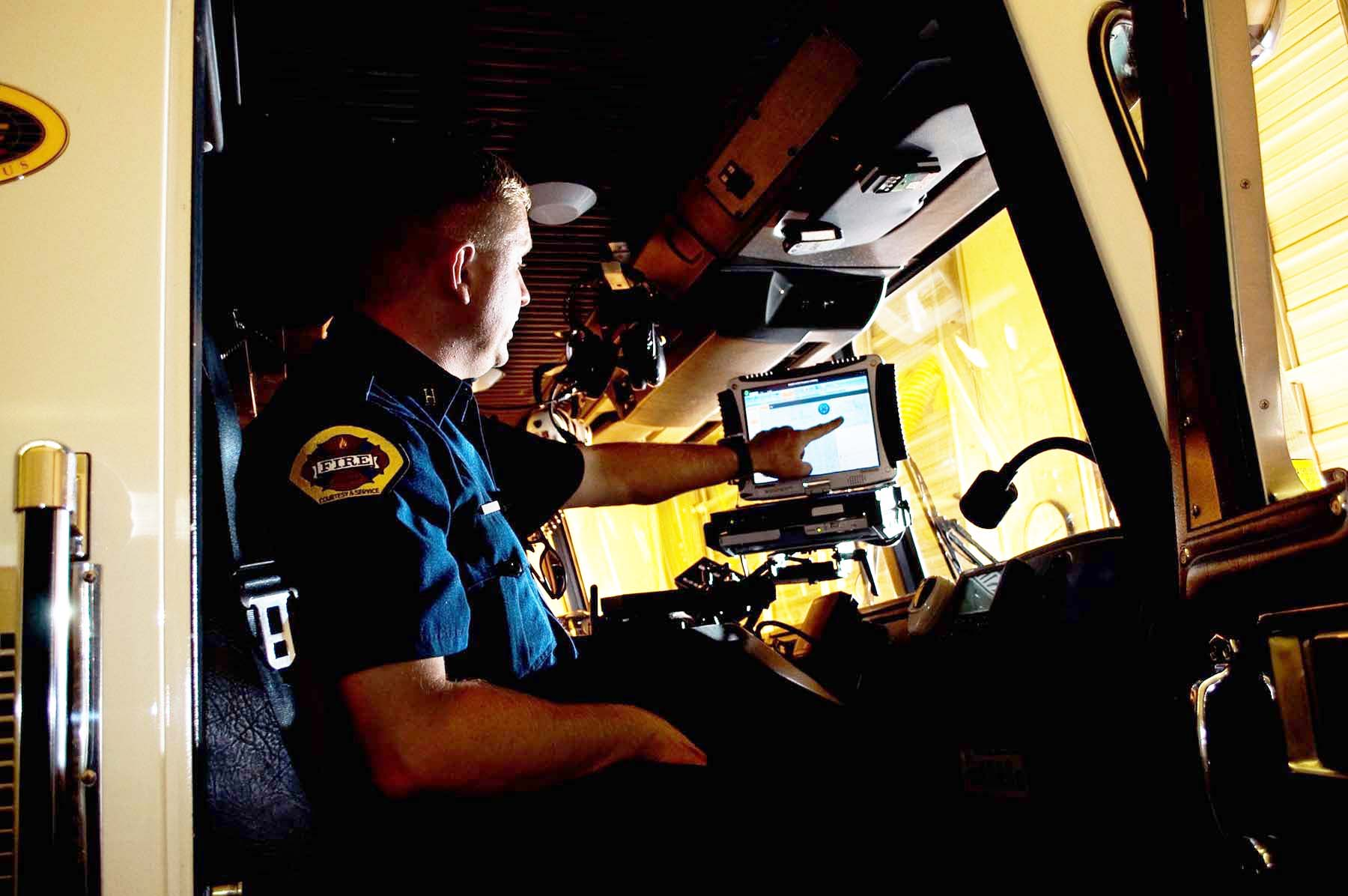 firefighter looking at a computer screen in an apparatus cab