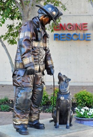 Life-size bronze sculpture depicts a firefighter and his canine partner ready to work.
