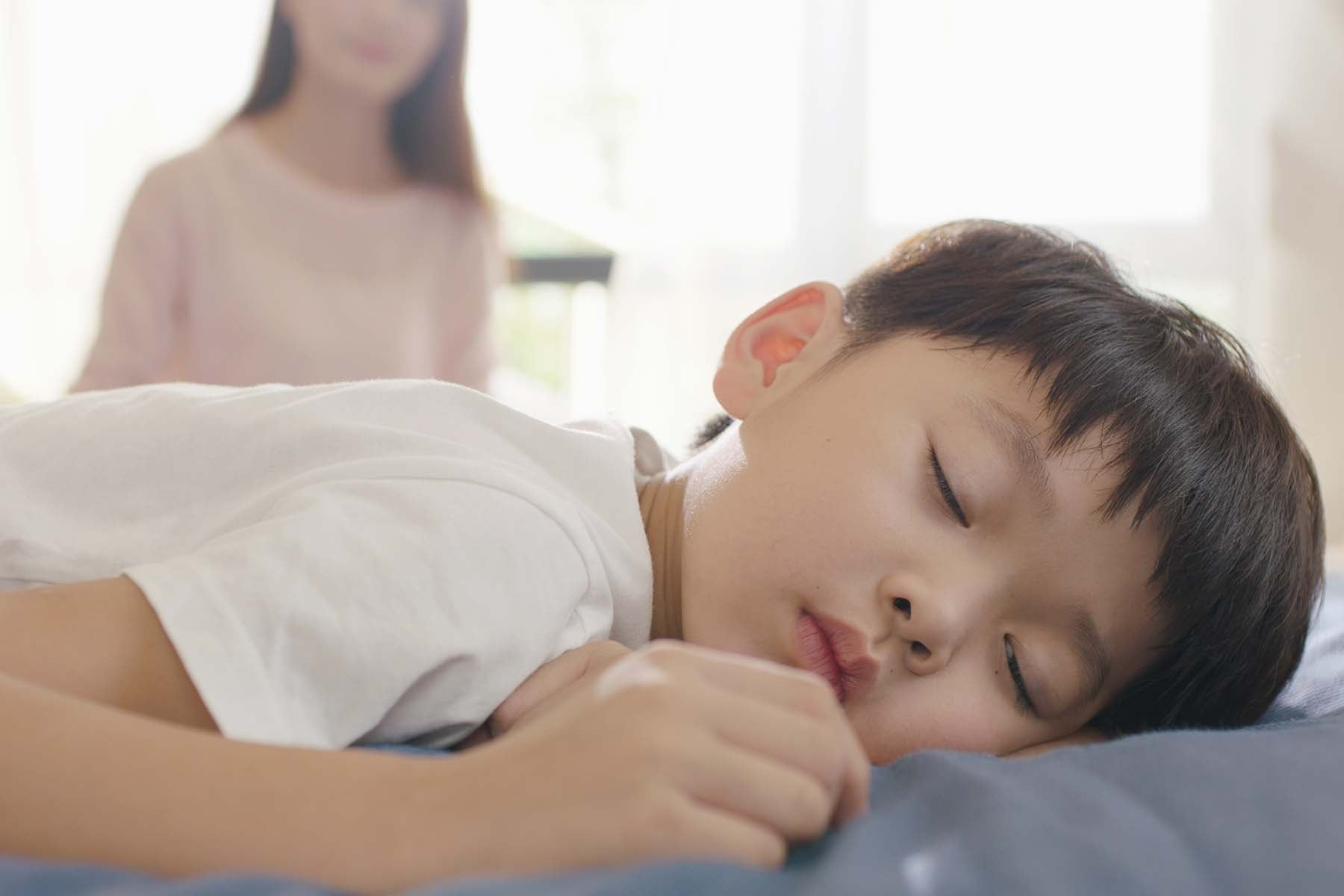 child sleeping with mother in the background