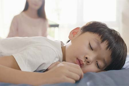 child sleeping with mother in background