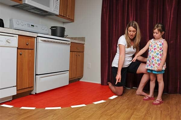 mother showing daughter to stay 3 feet away from the stove