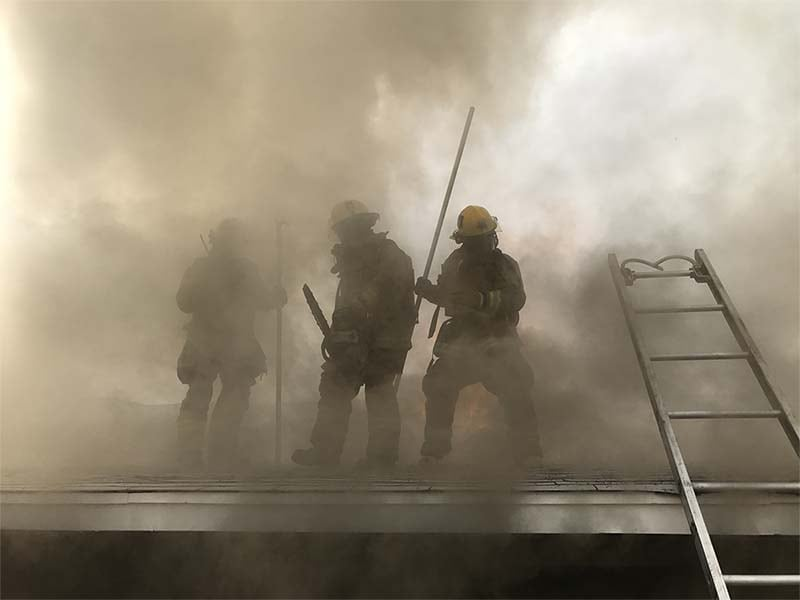 3 firefighters on a smokey roof