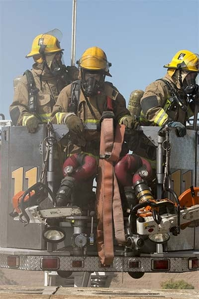 3 firefighters on a ladder apparatus