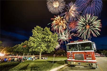 fire engine with fireworks in the background