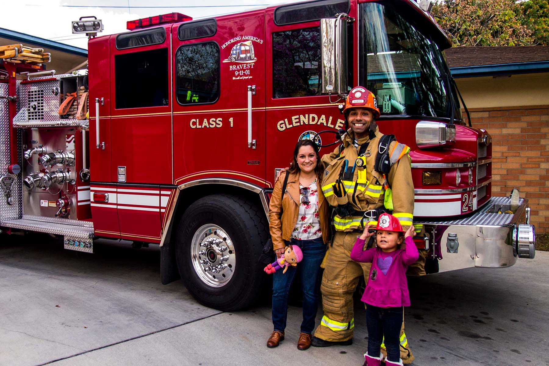firefighter with a mom and her daughter at the fire station