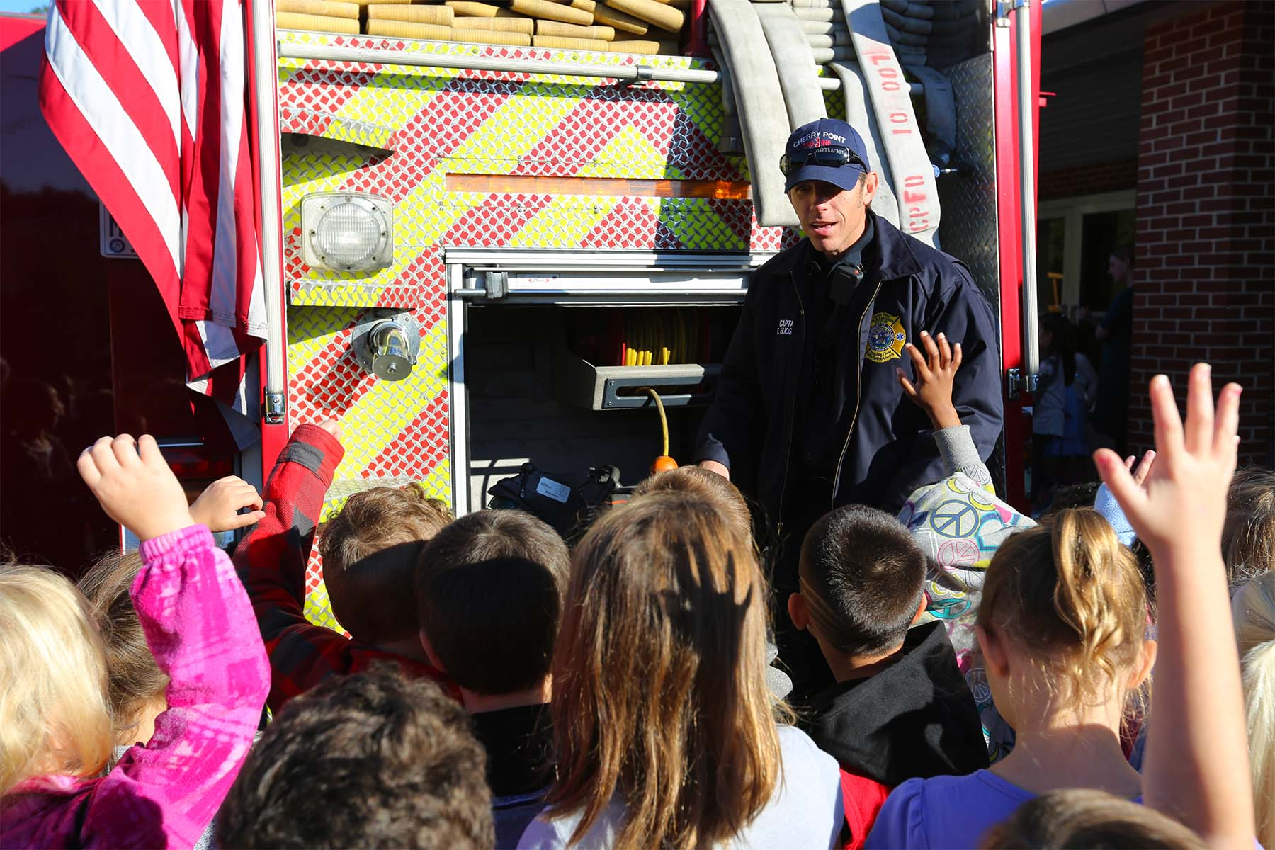 firefighter talking to children