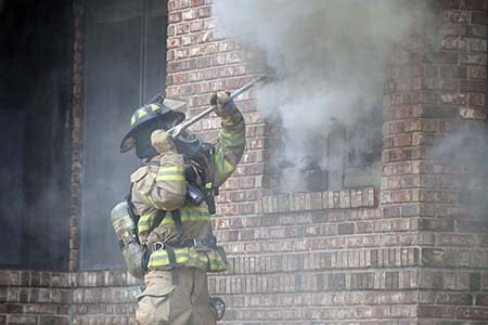 firefighter breaking a window