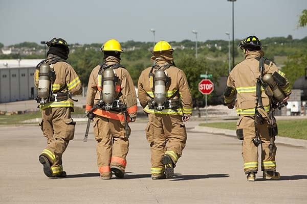 firefighters walking away in PPE after a fire