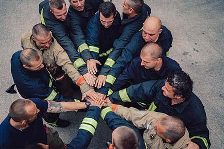 firefighters in a circle with stacked hands