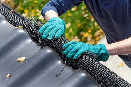 photo of person installing gutter guards