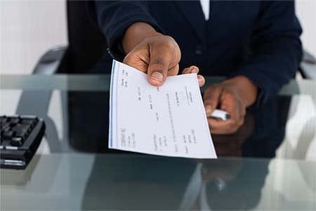 man extending his arm and holding a check